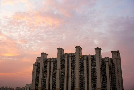 morning blue hour: Multistoried apartments in Gurgaon India against a colorful cloudy sky.