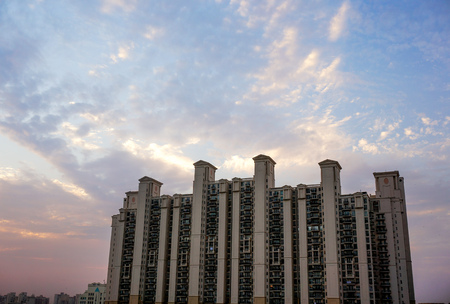 gurgaon: Multistoried apartments in Gurgaon India against a colorful cloudy sky.