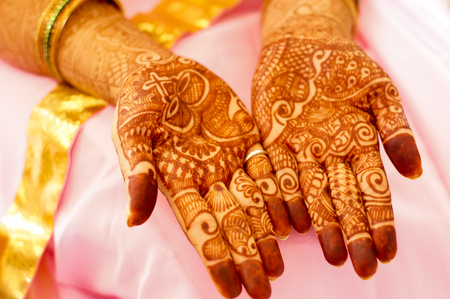 Mehendi henna used to decorate the palms of a woman in a pink saree. Mehendi is widely used in India and Pakistan during occassions like Diwali or Eid