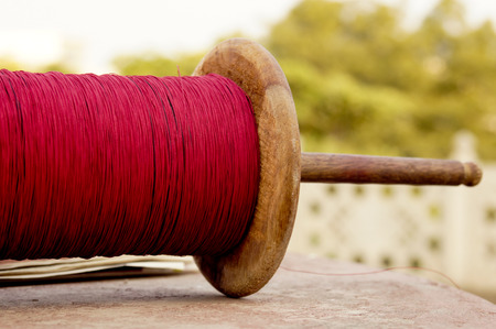 traditional sport: Spool of red glass covered thread used in the traditional sport of kite fighting in Rajasthan  Gurjrat