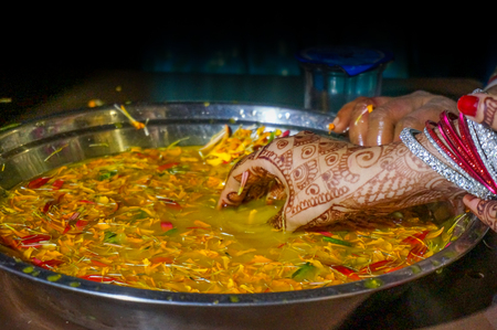 bangles hand: Indian bride soaking hands in turmeric water and flower petals as part of a ritual. This is a traditional ceremony in North indian weddings