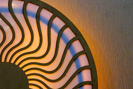 denote: Wooden design of two circles connected by wavy lines and lit by colorful lights. Can denote the circle of life, karma, the mstical divine connections