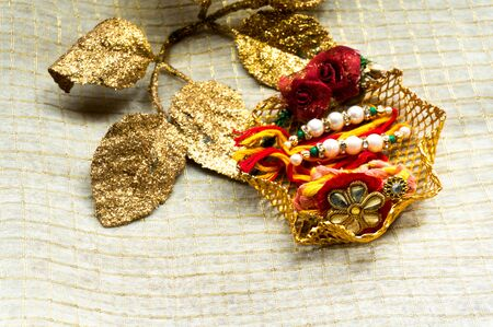 Rakhi threads put on a decorated stand with golden leaves to decorate it Stock Photo