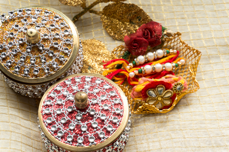 Rakhi thread with decorated boxes on a golden cloth. This is a collection of traditional items needed to celebrate the festival of rakhi