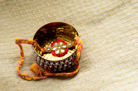 sybol: Rakhi thread packaged in a beautiful golden and red box. These are sent by sisters to their brother as a sybol of love