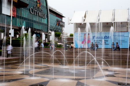 commercialization: Delhi, India; 6th July 2014: people sitting near the fountains of select citywalk mall in Delhi India. These malls have become popular hang out places for youngsters and familes alike