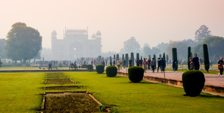 roaming: Agra, India, 24th Nov 2013: People roaming in the gardens of Taj Mahal with the entry gate for the compound visible behind them Editorial