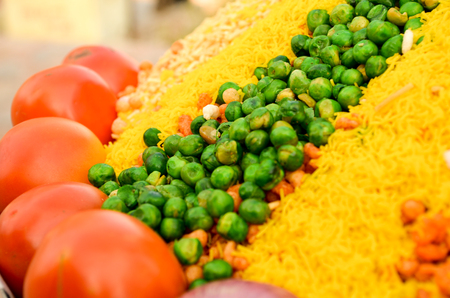 chaat: peas, tomatoes and sev for bhelpuri preparation. Closeup shot shot showing the ingredients and how they are displayed on streetside vendors Stock Photo