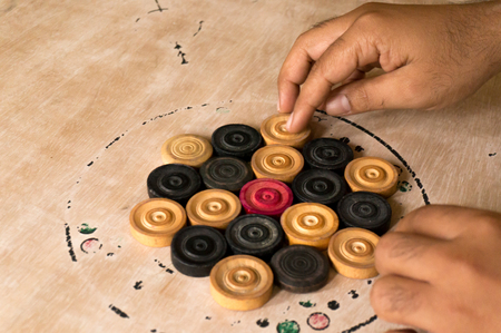 arranging: Hands arranging carrom men on the board prior to play