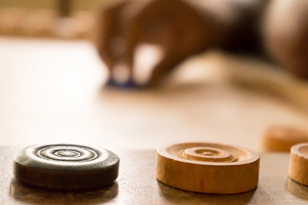 flick: Carrom men placed on the side with the player preparing to shoot