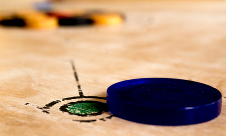 poised: Carrom striker poised for hitting the black and white men. Carrom is a very popular game played in the indian subcontinent. Stock Photo