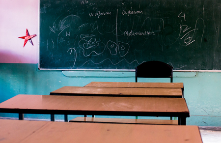 Wooden school benches facing a blackboard. Typical scene in a rural or small town school in India Stock Photo