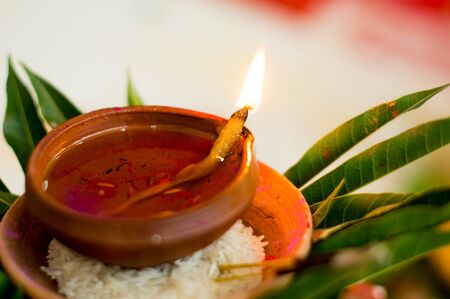 earthenware: Earthenware lamp filled with oil, placed on rice and leaves for a hindu ritual. These are done on diwali and marriage occasions Stock Photo