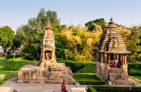 flank: Khajurao, India, 6th Dec 2015: Smaller temples flank the main temples in the UNESCO heritage site in Khajurao