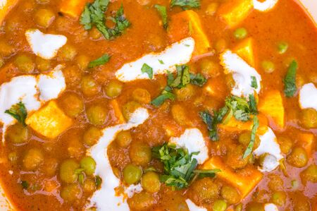 paneer: Indian dish of matar paneer, cottage cheese and peas, garnished with cream and fresh coriander. This is a special dish cooked for celebrations