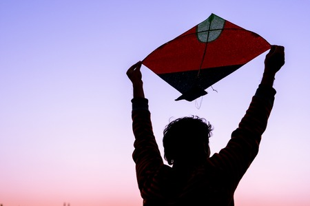 paper kites: boy holding a paper kite above his head at dusk. Silhouette shows the kites flown during makar sankranti, independence day and uttarayan kite festival