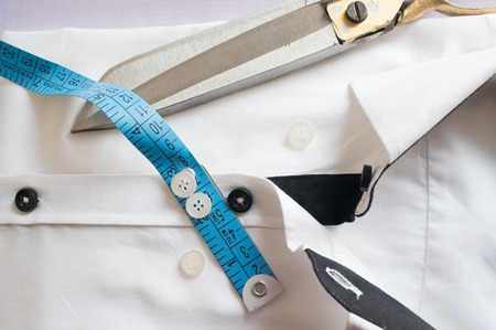 perfect fit: High key white shirt with measuring tape and scissors showing fitting, design, perfect fit and tailoring. Stock Photo