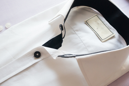 snug: White shirt with black collar and buttons. High key shot of beautiful white shirt for fashion or a classy look for men