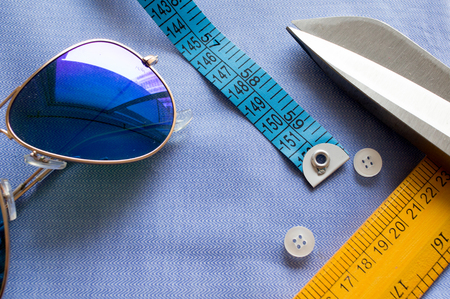 snug: Flat lay of items for modern fashionable clothing. Measuring tape, scissors, wooden scale and buttons on blue fabric Stock Photo