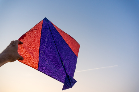 paper kites: Hand holding an indian kite against a blue sky. These are used in the sport of kite fighting