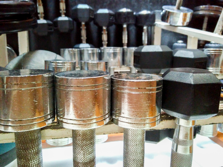 shiney: shiney metal dumbells on rack ready for an exercise session