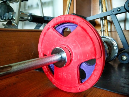 upmarket: barbells with red weights on gym floor denoting fitness and a new resolution
