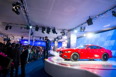supercar: DELHI, INDIA 6TH FEB 2016: Visitors look at a red ford mustang supercar at the Delhi Auto Expo 2016. This was one of the highlights of the auto expo