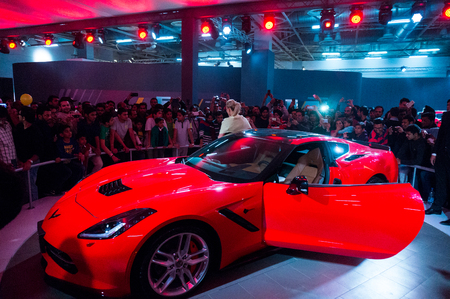 corvette: DELHI, INDIA 6TH FEB 2016: Visitors look at the red Chevrolet Corvette at the Delhi Auto Expo 2016. The chevy supercar was one of the main attractions of the expo