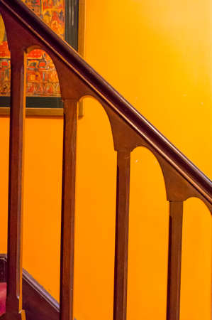 architectural interiors: Polished wooden railing against an orange wall. Interiors for an elegant mansion of architectural beauty
