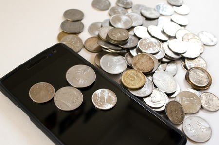 indian currency: Mobile phone with indian currency set on a white background. Denoting payment through mobile and mobile wallets. Pile of old and new coins with phone