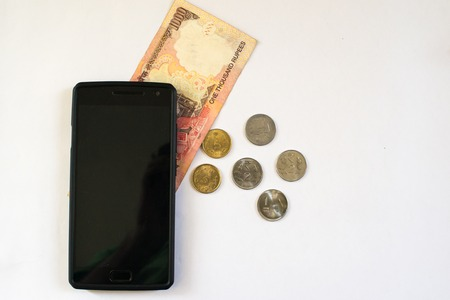 indian currency: Mobile phone with indian currency set on a white background. Denoting payment through mobile and mobile wallets