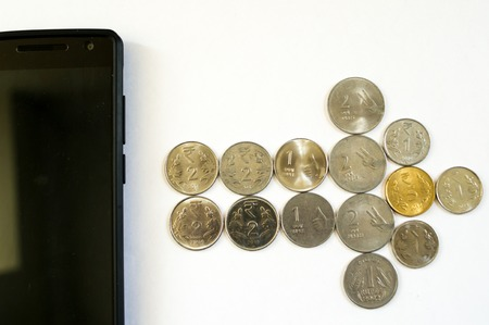 indian currency: Arrow of coins from mobile phone. Mobile phone with indian currency set on a white background. Denoting payment through mobile and mobile wallets