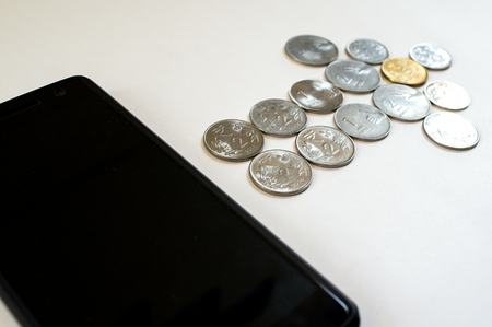 indian currency: Arrow of coins flowing from mobile. Mobile phone with indian currency set on a white background. Denoting payment through mobile and mobile wallets