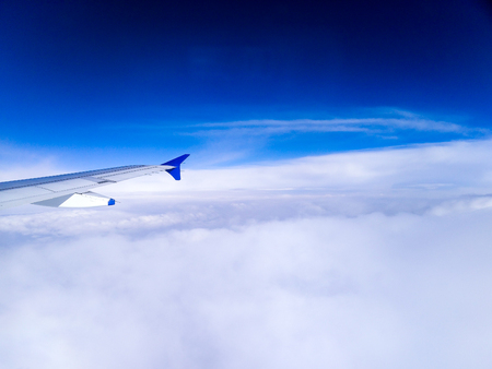 conveys: Aeroplane wing tip among clouds with blue sky and fluffy monsoon clouds. Conveys the joy of flight, travel and holiday