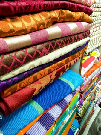 cloth manufacturing: Folded sheets of fabric with various prints and designs. These are typically used for making tailored garments Stock Photo