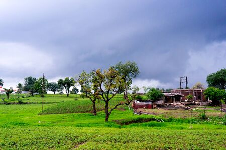 monsoon clouds: Monsoon clouds over fields and a storage shed in India. Stock Photo