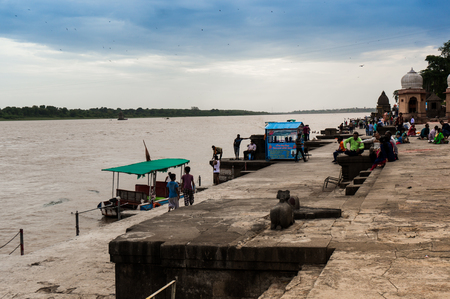 indore: Maheshwar, India - 16th July 2016: Riverbank at the Ahilya fort in Maheshwar near Indore. These boats are carry tourists over the river to show the fort
