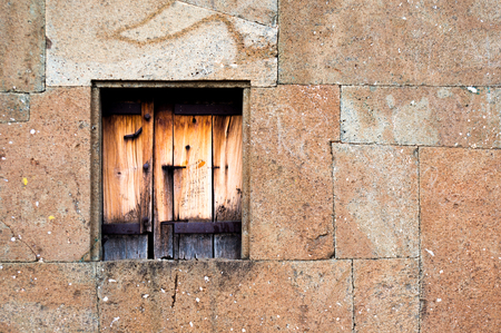 Closed wooden window in a stone wall. Both of them are broken with age but still there. Shows the strength of historical construction in india