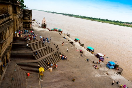 indore: Maheshwar, India - 16th July 2016: People climbing down the huge flight of stairs at the bank of the Narmada river from the Maheshwar fort in Madhya Pradesh