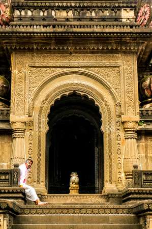 indore: Maheshwar, India - 16th July 2016: Pundit priest sitting at the entrance of an ornate hindu temple