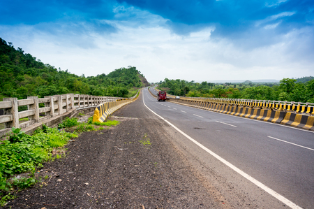 bordered: Long stretch of empty road bordered with tree filled hills and under beautiful monsoon skies. Showing a great way to explore india via the well developed road network