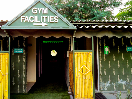 punjab: Direction to a rural village gym marked on a wood and bamboo building in India Stock Photo