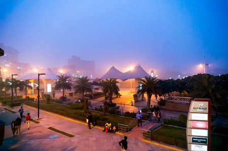 owing: Delhi, India - 6th Nov 2016: Foggy smog filled evening at Select citywalk shopping mall in Delhi. This popular hangout place was empty owing to the dense pollution Editorial