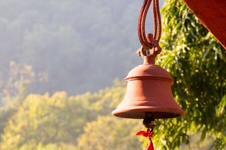 ourdoor: Hindu prayer bells in a remote temple in the forest with the bokeh of the trees and golden sunlight from a morning sun Stock Photo
