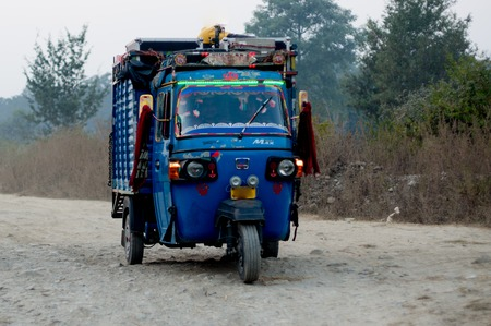 ourdoor: Jim Corbett - 19th Nov 2016: Blue autorickshaw used for transporting goods and people in most of India. Travelling on a rough mountain path