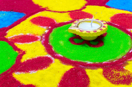 Indian earthenware and wax lamp, diya, set in the center of a colorful ground painting called rangoli. Usually put in the hindu festival of Diwali Stock Photo