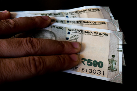 recently: Person holding the new indian Rs 500 note isolated on black. These new currency notes have been recently authorized by the government Stock Photo