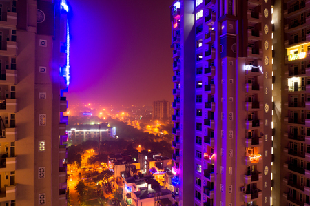 gurgaon: colorful lights on a skyscraper in Noida Delhi India on the eve of diwali. Urbanization of the city has given a rise to many residences Stock Photo