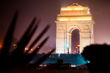 india gate: India gate at night with multicolored lights. This landmark is one of the main attractions of Delhi and a popular tourist destination. It was designed by Edwin Luytens Stock Photo