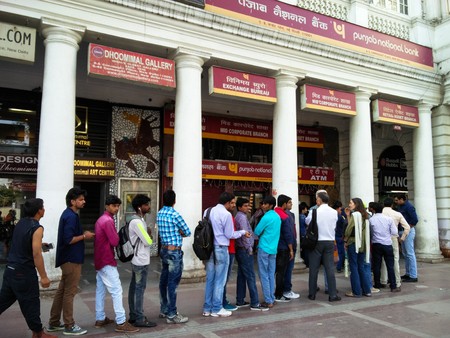 Delhi, India - 26th Nov 2016: People stand in a queue outside a bank ATM in Connaught Place Delhi post banning of the Rs.500 and Rs.1000 currency notes Editorial